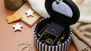 A close up of a jewellery box with 4 gold rings, a gold necklace and 2 gold earrings